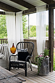 Black rattan chair on roofed terrace with curtains