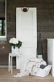 Altes Türblatt und Deko in Weiß im Landhausstil auf der Terrasse