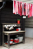 Garland of fabric remnants in shades of red above outdoor play kitchen