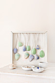 Arrangement of seashells dyed blue and green and hung in deep picture frame