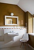 White chair next to sink in bathroom with cinnamon-brown wall
