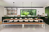 Long dining table, bench and chairs in front of dark green kitchen counter