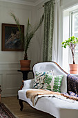 Classic recamier couch below window in living room with panelled walls