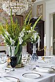 Strauß aus weißen Gladiolen, Farn und Goldrute auf gedecktem Tisch