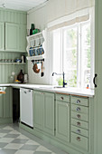 Mint-green country-house kitchen with chequered floor