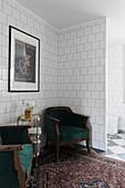 Dark green velvet armchair and rug in seating area in bathroom