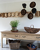 Hats hung on antlers and row of hat pegs above console table in hallway