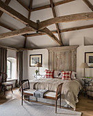 Classic bedroom in beige with exposed roof structure and wooden roof beams