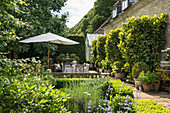 Summery, English-style garden with terrace adjoining stone house