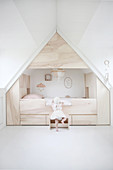 Child climbing into modern cubby bed surrounded by storage in attic bedroom