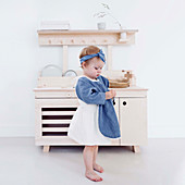 Little girl standing in front of pale wooden play kitchen