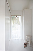 Pretty blouse hanging in window with airy curtains in white interior