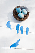 Blue-dyed eggs in Easter nest on tablecloth with stencilled bird motif