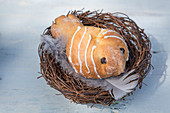 Hen-shaped sweet bun in Easter nest of twigs