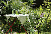 Tablecloth hand-decorated with fern motifs on garden table