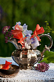 Posy of sweet peas, astrantia and lady's mantle in silver jug