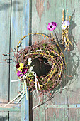 Wreath of moss and twigs with posies of violas hung on door