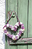 Heart-shaped wreath of lilac hung from door