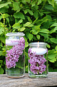 Candle lanterns made from preserving jars filled with water, lilacs and floating candles
