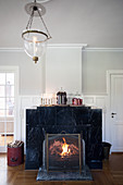 Fire burning in open fireplace with black marble surround