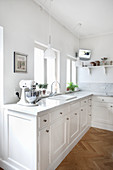 Classic white kitchen with panelled doors and herringbone parquet floor