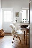 Stühle mit Fell am Holztisch in ländlicher Küche in Weiß