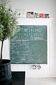 Tafel an der Wand mit Holzverkleidung und Kinderbildern