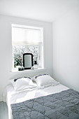 Bed below window in simple, white bedroom