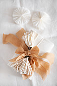 Wrapped gift decorated with handmade tassels and fabric ribbon