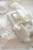 Gift wrapped in fabric decorated with fabric ribbon and paper rosettes