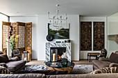 Exotischer Stilmix im Wohnzimmer mit offenem Kamin aus Marmor
