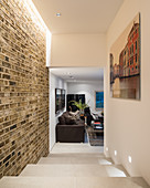 Brick wall and steps in hallway leading to masculine living room