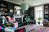 Eccentric living room with dark walls and colourful accessories
