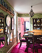 Deep pink rug and green floral wallpaper in classic dining room