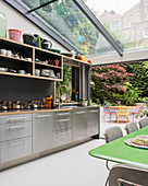 Modern kitchen and dining table below glass ceiling with garden access in background