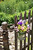 Sommerstrauß im Einmachglas an Gartenzaun gebunden