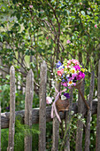 Rusty kitchen utensils decorating garden fence and bouquet in old funnel