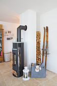 Firewood stacked in niche behind wood-burning stove in living room