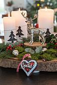 Rustikaler Adventskranz auf einer Baumscheibe mit Moos