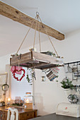 Christmas decorations on shelf suspended from ceiling in rustic kitchen