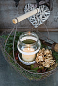 Candle in screw-top jar with lace trim in wire basket