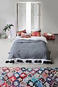Colourful rug in front of bed with tasselled, ethnic-style bedspread