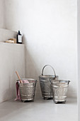 Silvery metal buckets with Oriental patterns in bathroom