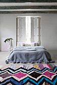 Bed below window with shutters in Bohemian-style bedroom