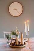 Schale mit natürlicher Weihnachtsdeko und Kerzen auf dem Tisch