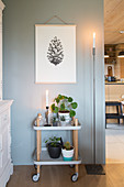 Plants on modern serving trolley below poster of pine cone on grey wall