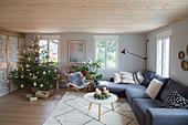 Grey corner sofa and Christmas tree in rustic living room