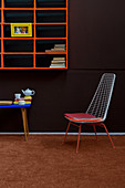 Metal chair below orange shelves on brown wall