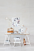 Desk on trestles and pinboard in study decorated in white