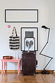 Decorative still-life arrangement of pink stool, old trunk and jointed standard lamp